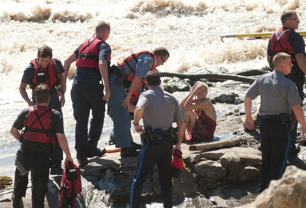 Emergency response personnel comfort Susan Hamlet who was removed from underneath the spillway following a water rescue Friday, Sept. 24, 2010, on the north side of the Kansas River.