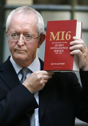 "Keith Jeffery poses with his book "" MI6: The History of the Secret Intelligence Service 1909-1949,"" after a news conference to launch the book Tuesday at the Foreign and Commonwealth Office in London. Jeffery is the first to be granted complete access to the MI6 archives for the period of history covered by the book."