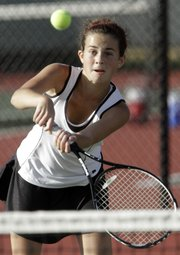 Lawrence High's Nikki Carmody makes her way to the net for a return on Monday at the Lawrence High Tennis Center.