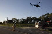 A Life Star helicopter takes off from the scene of a single-vehicle rollover accident along the Farmers' Turnpike between Lecompton and Lawrence. Meanwhile, a firefighter attends to the accident scene.
