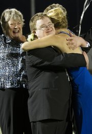 Owen Phariss recieves a hug from Audrey Hughes as his mother, Nancy Holmes celebrates, after Phariss was named homcoming king Friday night during halftime of the Free State football game against Shawnee Mission East. Hughes played a huge role in getting Phariss on the ballot for homecoming king.