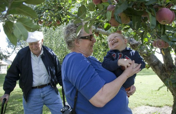 Trestle Wrencik, 2, delights in picking an apple out of a tree with the help of his grandmother Vicky Logan, Kansas City, Mo., at the Vertacnik Orchard during the Kaw Valley Farm Tour in 2010. At left is Trestle's grandfather Jay Logan.