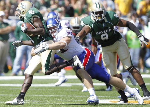 Kansas defensive end Jake Laptad wraps up Baylor receiver Kendall Wright for a loss in the backfield during the second quarter Saturday, Oct. 2, 2010 at Floyd Casey Stadium in Waco. At right is Baylor tight end Brad Taylor.