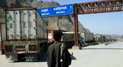 A Pakistani border guard stands near Afghanistan-bound NATO trucks parked on the roadside Friday in Pakistani tribal area of Khyber. Pakistan closed the Khyber Pass supply route for U.S. and NATO troops in Afghanistan on Thursday.