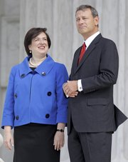 Chief Justice John Roberts and Justice Elena Kagan stand for photographers after a formal investiture ceremony for Kagan on Friday at the Supreme Court in Washington.