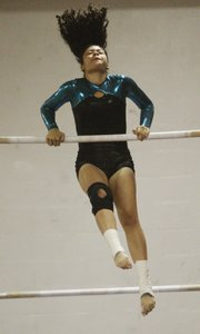 Lawrence High gymnast Tawney Carter competes on the uneven bars Monday at Lawrence High.