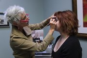 Pam Biemick works on client Regan Lehman Pillar recently as Biemick showed her client how to use a primer and concealer.