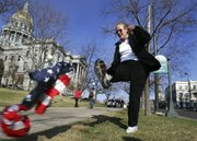 "Margie Phelps, daughter of the Rev. Fred Phelps of the Westboro Baptist Church in Topeka, kicks a U.S. flag on the grass outside the Colorado State Capitol during a rally for the ""Right to Rest in Peace"" rally in Denver in this March 23, 2006, file photo. Phelps is set to go before the U.S. Supreme Court today to represent her church in a case that tests the scope of free speech protections under the Constitution's First Amendment."
