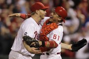 Philadelphia starting pitcher Roy Halladay, left, celebrates with catcher Carlos Ruiz after throwing a no-hitter against the Reds on Wednesday in Philadelphia.