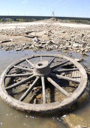 A wagon wheel sits in a low-water area of the Kaw River.