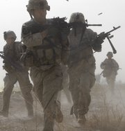 A U.S. soldier returns fire as others run for cover during a firefight with insurgents in the Badula Qulp area, west of Lashkar Gah in Helmand province, southern Afghanistan, near Marjah, in this Feb. 14, 2010, file photo. U.S. Marines were conducting an offensive against the Taliban.