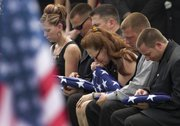 Beverly A. Crow, center, sits with unidentified family members during the funeral for her husband, Missouri Army National Guard Sgt. Robert Wayne Crow, in Liberty, Mo., in this July 19, 2010, file photo. Sgt. Crow, 42, of Kansas City, Mo., died July 10 in Paktika, Afghanistan, of wounds suffered when insurgents attacked his vehicle with an improvised explosive device. He was a combat engineer with the 203rd Engineer Battalion headquartered in Joplin, Mo.