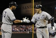 New York's Alex Rodriguez (13) congratulates Mark Teixeira after Teixeira hit a two-run home run. The homer proved to be the difference in the Yankees' 6-4 victory over the Twins on Wednesday in Minneapolis.