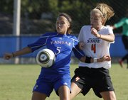 KU's Kortney Clifton (5) controls the ball against Oklahoma State's Colleen Dougherty (4).