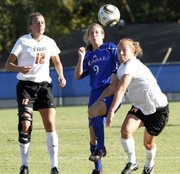 Kansas' Jordyn Perdue (9) battles Oklahoma State's Kristen Kelly (12) and Sarah Brown for a possession.