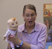 "Priscilla Howe, Lawrence, sings ""The Itsy Bitsy Spider"" with the help of a puppet Saturday at the Lawrence Public Library's River City Reading Festival. Next month, voters will decide the fate of a tax increase that would help fund an $18 million expansion of the library."