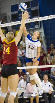 Kansas University middle blocker Jenna Kaiser (12) hammers a spike against Iowa State. The Jayhawks upended the No. 10 Cyclones, 3-1, on Saturday at Horejsi Center.