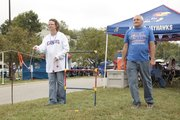 Tammi Peterson, Dallas, and John Hosler, Valley Falls, enjoy a toss game while tailgating with friends outside Memorial Stadium before the start of recent home game last month.