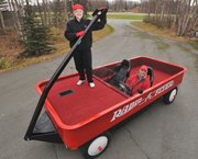 Judy Foster and Fred Keller of Wasilla, Alaska, pose Monday in the couple's giant red Radio Flyer wagon. A converted pickup, the wagon is fully operational and licensed for road travel.