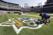 Texas Rangers grounds crew employee Don Crymes puts the final touches on the American League Championship Series logo on the field at the Texas Rangers Ballpark on Wednesday in Arlington, Texas.