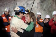 Miner Raul Bustos embraces an unidentified woman Wednesday after after being rescued from the collapsed San Jose gold and copper mine where he had been trapped with 32 other miners for over two months near Copiapo, Chile, in this photo released by the Chilean government.
