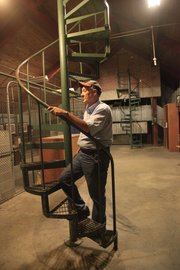 Gary Confer, who oversees custodial operations of Fraser Hall, enters a cupola via a spiral staircase on the top floor.