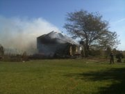 Firefighters spray water on a house fire in the 200 block of Highway 40 southwest of Lecompton on Thursday, Oct. 14.