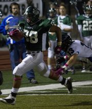 Firebird running back Henry Vaeono tries to escape a Ravenr defender during their game Friday night at Lawrence Free State Stadium.