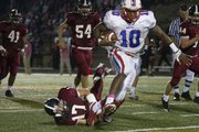 Eagle quarterback Victor Simmons (10) breaks a tackle during their game Friday night at Lawrence High School Stadium.