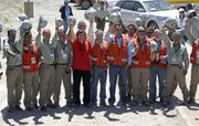 Chile's Mining Minister Laurence Golborne, fifth from left, poses for photos Thursday with the team of mine rescuers that took part in the rescue operation of the 33 trapped miners, at the San Jose mine near Copiapo, Chile.