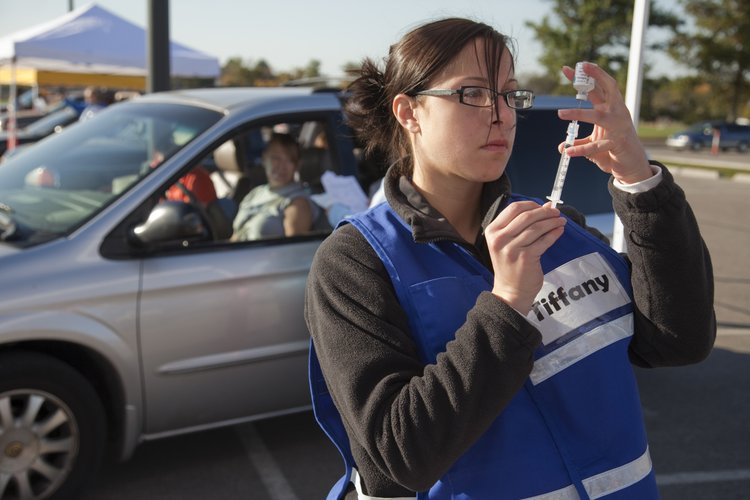 Volunteer Tiffany Belland, a student in Kansas University's School of Pharmacy, gets a flu shot ready during a drive-thru flu shot clinic in 2010 at KU's Park and Ride Lot, Clinton Parkway and Iowa Street.