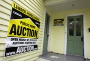 A home has a foreclosure auction sign displayed  Sept. 22 in Chagrin Falls, Ohio.