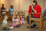 Betty Pickerel, an educator with Lawrence Memorial Hospital, reads a story about having a new brother or sister to children participating in a Tyke Hyke class given in October 2010. From left are Evan Torres, 4; Jolie Mcwhirt, 5; Addison Ediger, 4; and Anne Cross, 3.