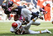 Houston tight end Owen Daniels (81) flies over Kansas City Chiefs defenders Donald Washington (27) and Jovan Belcher after a fourth-quarter catch.