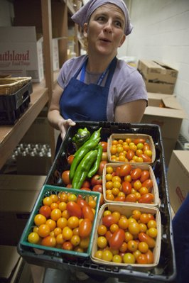 Wendy Green, assistant manager of food service at West Junior High School, holds a tray of vegetables that were picked from the school's garden. Cafeteria staff members will chop them up and put them on the food bar.