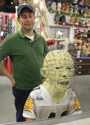 Brad Barrett watches as his son, Chance Barrett, 8, tries on a mask at Fun and Games.