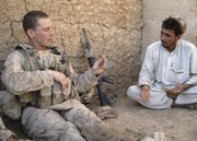 U.S. Marine Sgt. Jeffrey Benson, left, of Medina, Ohio, holds a spent bullet casing found after a gun battle while he interrogates a resident of Marjah, Afghanistan, in this Sept. 26, 2010, photo.  In this southern Afghan town that coalition forces seized from Taliban fighters eight months ago and are still very much clearing, American troops don't have to go far to find the insurgency. But finding insurgents is another story altogether.