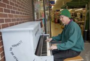 Doors were open for business Tuesday at Cottin's Hardware & Rental, 1832 Mass., but it was all boogie-woogie for Bradford Hoopes, Lawrence, as he pounded out a tune on a painted piano outside the store. Melissa Warren, a piano technician at Kansas University, fixed up the upright piano and arranged to have it placed at Cottin's. Warren hopes to place more pianos around town for members of the public to play.