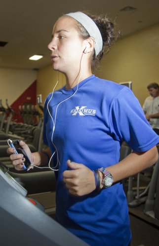 Dru Huff listens to music on her iPhone as she exercises recently at Maximus Fitness Center, 3400 S. Fourth St.