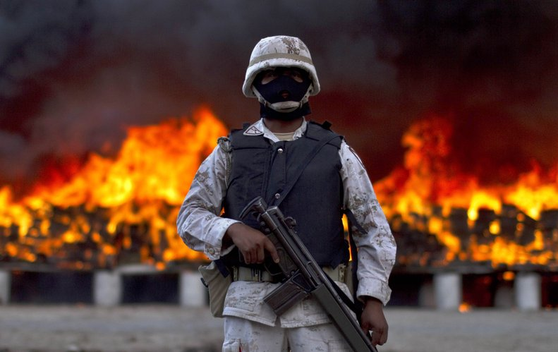 A soldier stands guard next to packages of marijuana that are being incinerated Wednesday in Tijuana, Mexico. On a conjoined operation with the army, local and state police seized 134 tons of U.S.-bound marijuana Monday, by far the biggest drug bust in the country in recent years. Eleven suspects were detained.