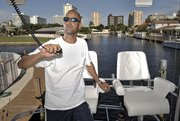 Former mortgage industry executive Jason Altneu, pictured Aug. 17 in South Florida on his boat, now has two jobs: charter boat captain and independent insurance agent. He's one example of what former construction and mortgage industry workers are doing to transition into new work.