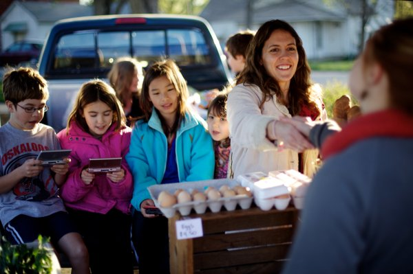 Megan Paisley of Double J Farm in Fontana is proud that she's introduced her daughters, including Josie, second from left, to farming. Paisley sells produce, breads, canned items and soaps at the Saturday Lawrence Farmers' Market.
