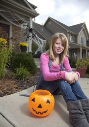 Twelve-year-old Elizabeth Patton, pictured outside her Lawrence home, recently delivered $200 of donations she gathered to Douglas County CASA so portions of the money could be distributed to local kids who can't afford Halloween costumes. Patton spent the last two months gathering money by selling baked goods and babysitting.