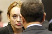 Lindsay Lohan looks at a court official as she arrives for a probation violation hearing Friday at Beverly Hills Courthouse in Beverly Hills, Calif.