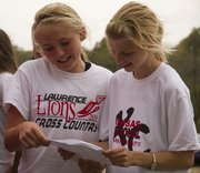 Lawrence High cross country teammates Emily McEntire, left, and Grace Morgan, look over their race results after running in the 6A regionals cross country meet Saturday afternoon at Haskell Indian Nations University. The Lawrence High girls placed third as a team with a time of 1:27:06.48.