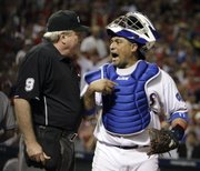 Texas Rangers catcher Bengie Molina, right, argues with home-plate umpire Brian Gorman on Friday in Arlington, Texas. Molina will face his old team, the San Francisco Giants, when the World Series begins play Wednesday.