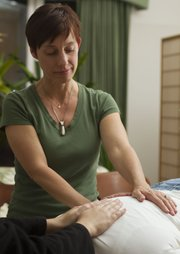 Marta Schwartz gives reiki to Nadine Koch at a recent Lawrence Reiki Circle meeting.
