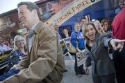 Republican gubernatorial candidate Sam Brownback and Rep. Lynn Jenkins greet a crowd of supporters as they exit the GOP candidate bus in Lawrence on Wednesday. The Kansas Republican Party's bus tour stopped by congressional candidate Kevin Yoder's Lawrence headquarters, 123 W. Eighth St.