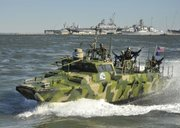 In this photo released by the U.S. Navy, sailors assigned to Riverine Group 1 conduct maneuvers aboard Riverine Command Boat (Experimental) (RCB-X) at Naval Station Norfolk, Va., on Friday. The RCB-X is powered by an alternative fuel blend of 50 percent algae-based and 50 percent NATO F-76 fuels to reduce total energy consumption on naval ships.