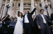 Argentina's new president Cristina Fernandez, left, and her husband, Argentina's departing President Nestor Kirchner, wave after Fernandez was sworn in at the National Congress in Buenos Aires, Argentina, in this Dec. 10, 2007, file photo. Kirchner died Wednesday of a heart attack at age 60.
